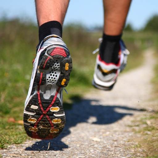 Trail running. Freeze action closeup of man running. Shallow depth of field, focus on left shoe.